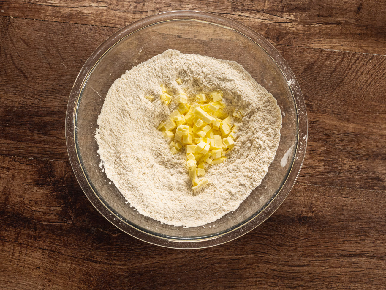 Mix together flour, brown sugar, baking powder, and salt in a large bowl. Once combined, cut in the butter with a fork or pastry cutter until the mixture resembles coarse crumbs.