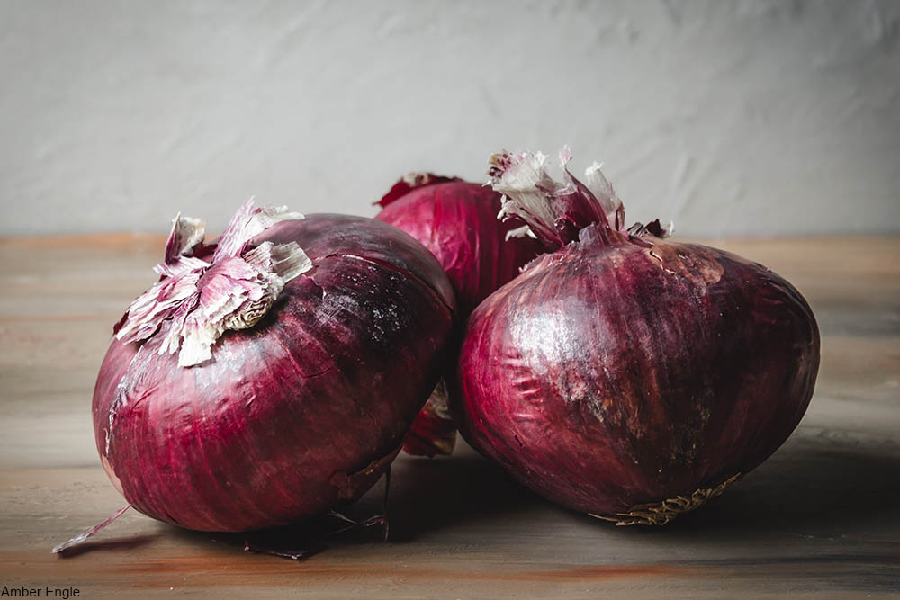 three red onions on a cutting board