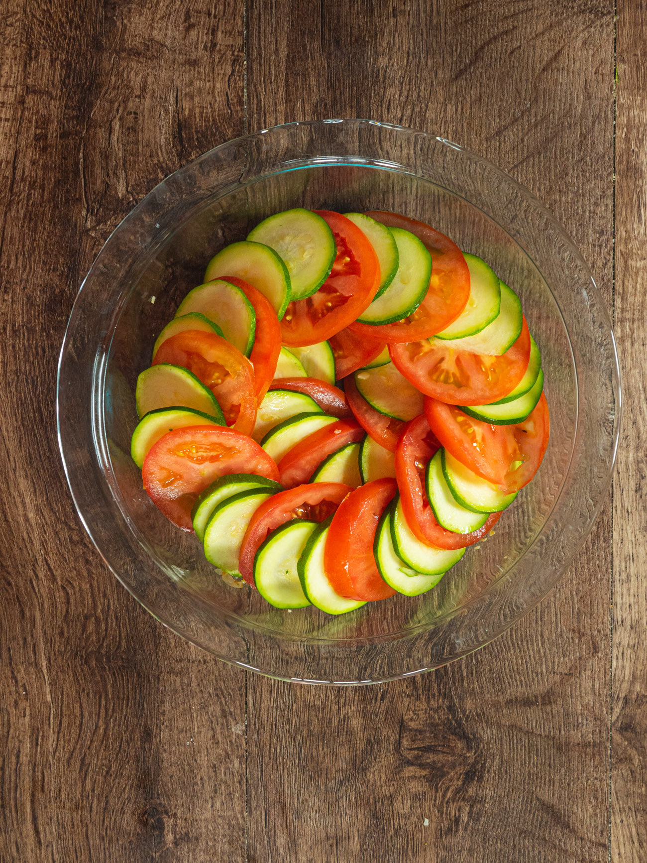 Layer tomatoes and zucchini slices in a circle, alternating a layer of 2 zucchini slices and 1 tomato slice until the dish is filled.