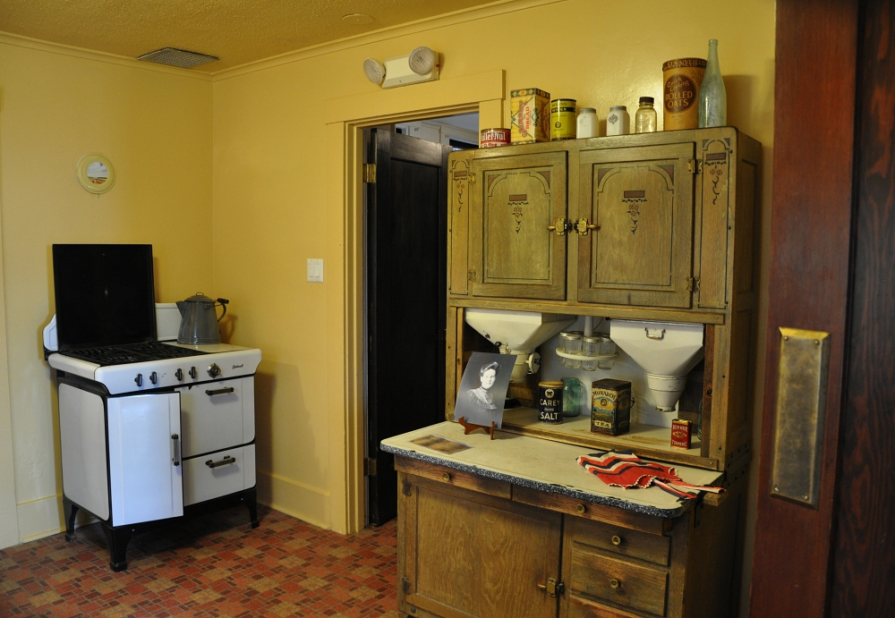 recreation of a turn of the century kitchen with an enameled stove and a Hoosier cabinet