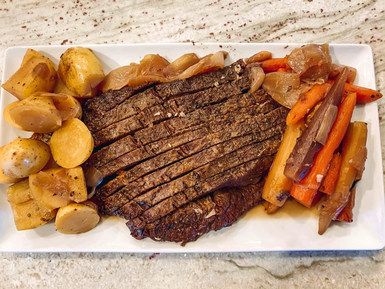 Slice the brisket against the grain, serve with veggies and potatoes. Enjoy!