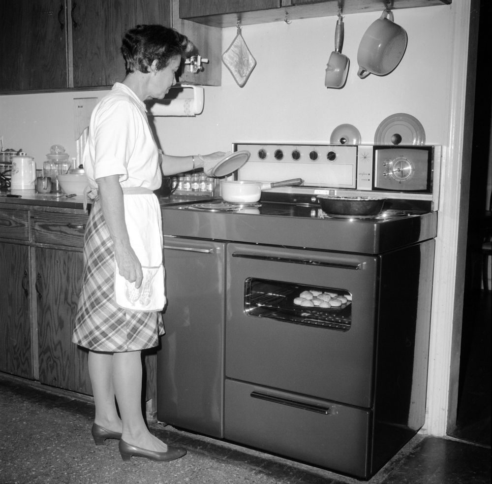 woman cooking over a stove, 1950s or 1960s