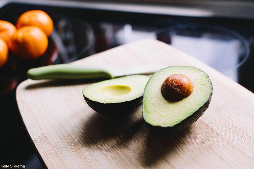 avocado cut in half on cutting board