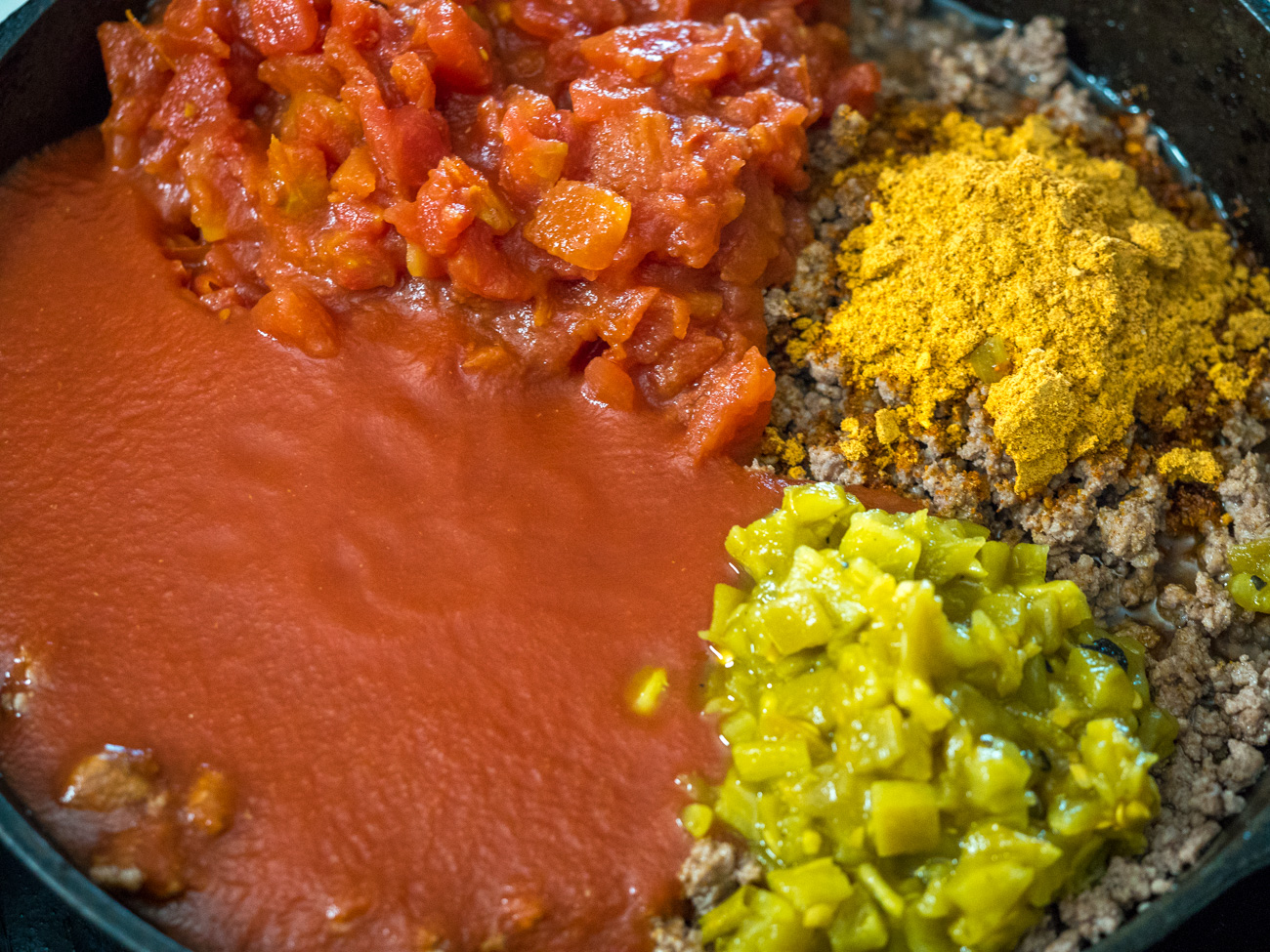 Return meat to skillet and taco seasoning, seasoned salt, diced tomatoes, tomato sauce, and chopped green chilies. Reduce heat and simmer, uncovered for 15-20 minutes.