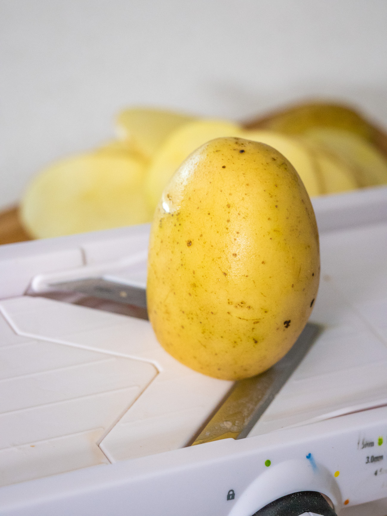 potatoes being sliced on a mandoline