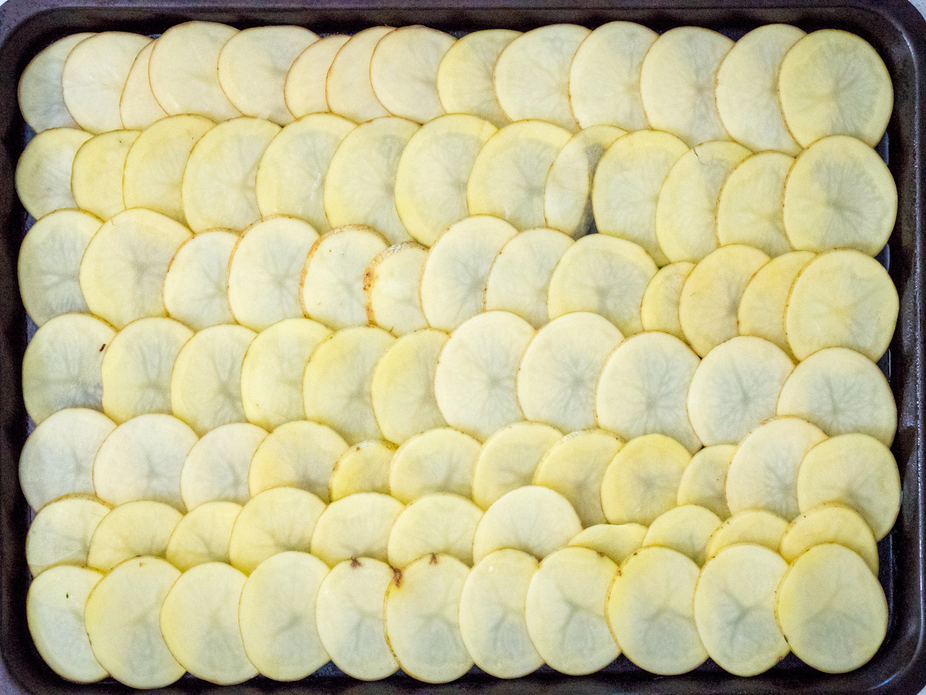 Lay out potato slices on sheet pan in rows, slightly overlapping each other.