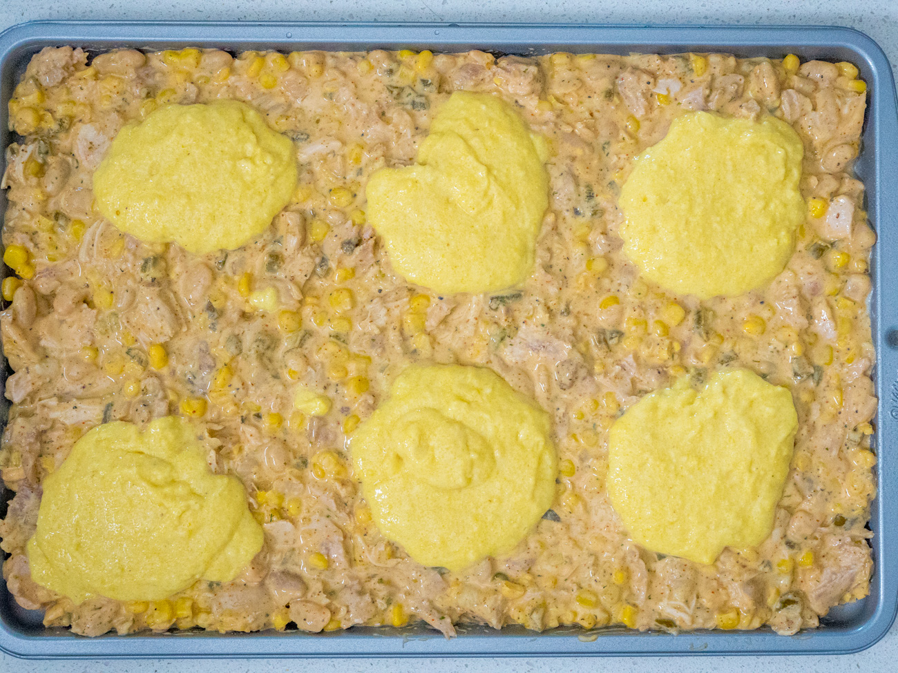 Place 2-tablespoon dollops of cornbread batter on top of chili in 6-8 mounds. Top each cornbread mound with remaining  Monterey Jack cheese.