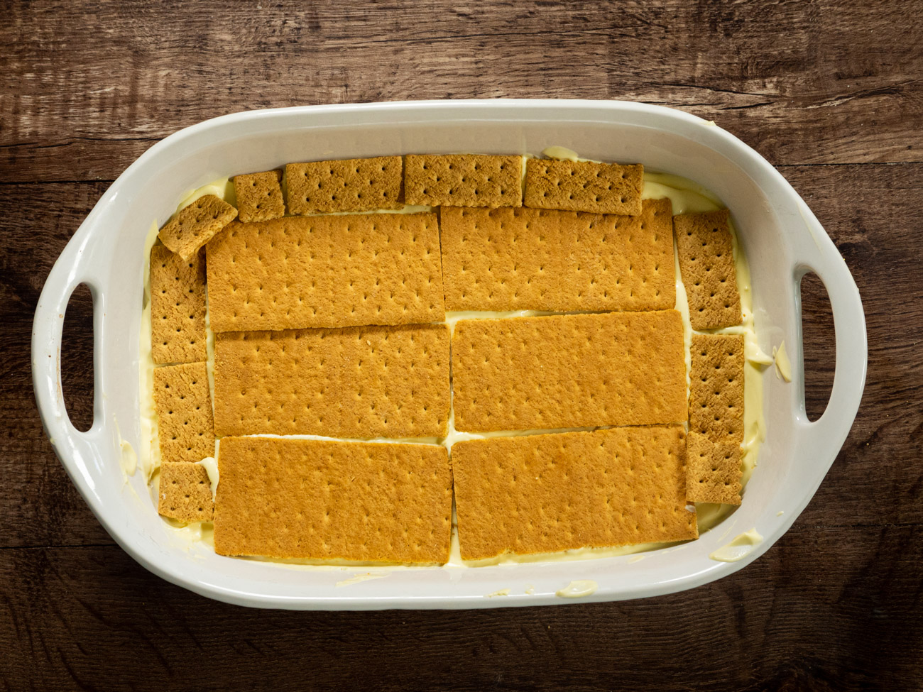 Top with another layer of graham crackers and then pour the rest of the pudding on top of that. Use a knife, rubber spatula, or offset spatula to smooth top pudding layer.