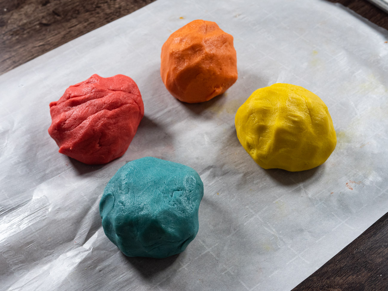 Cut dough into 4 equal sections (or less if using fewer Jello flavors). Add 2 tablespoons of Jello to each quarter and knead until color is even. Use food coloring if colors aren't as vibrant as you'd like. Use gloves for the steps that involve Jello and/or food coloring to avoid staining your hands.