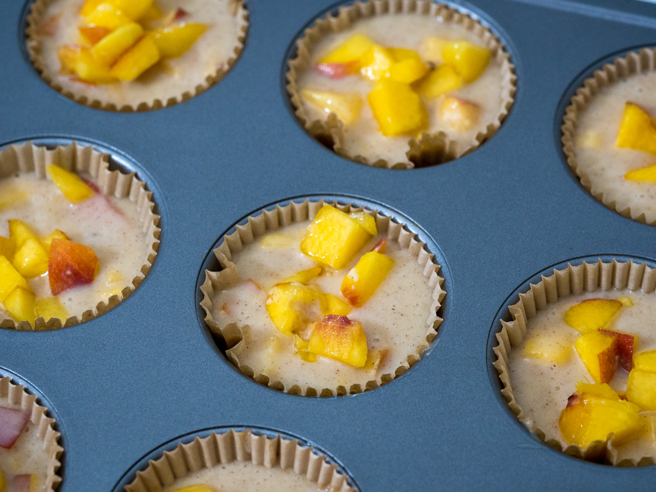 Portion the batter into the muffin cups before moving on to the topping.