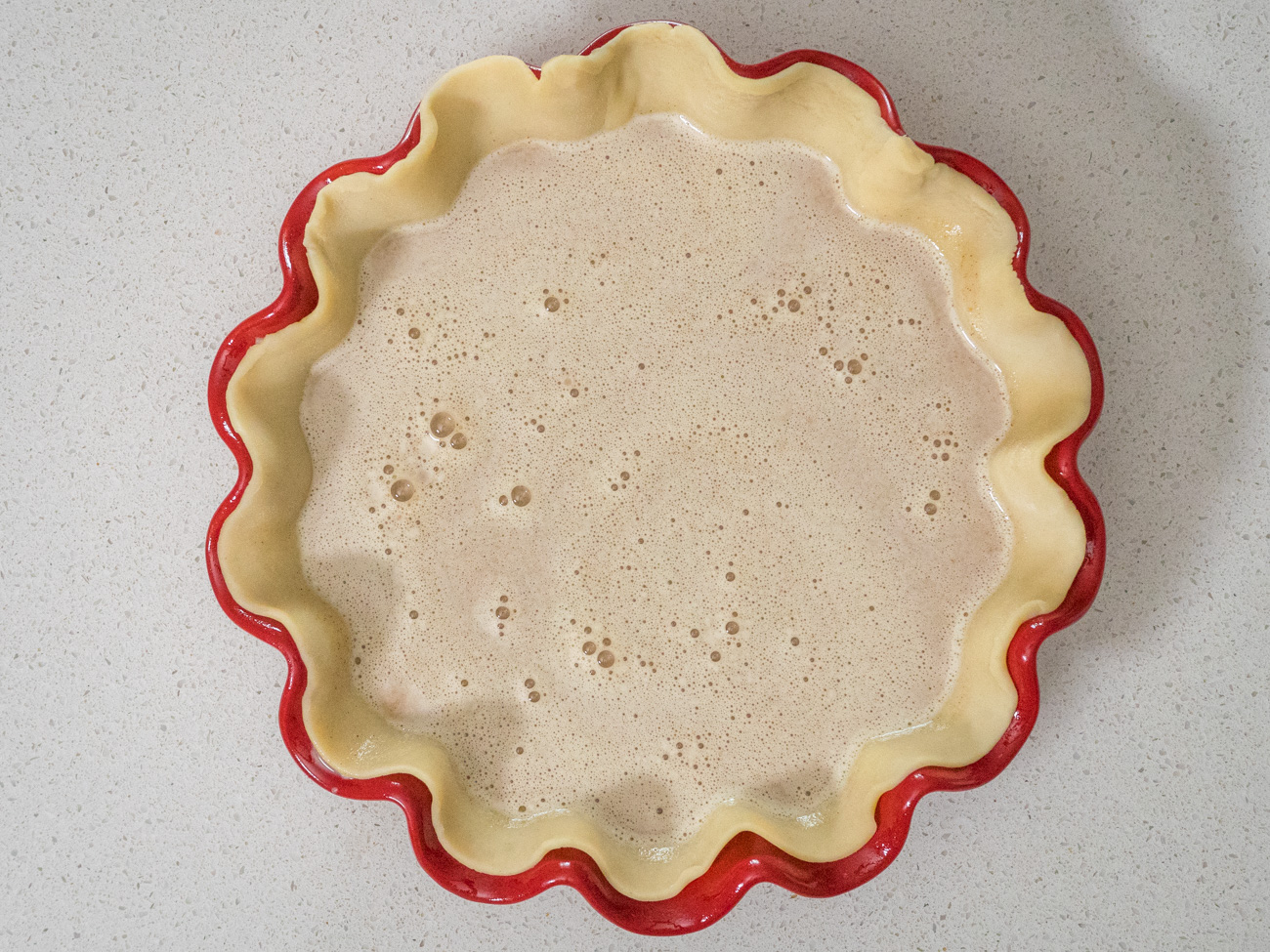 Pour filling into unbaked pie crust, using a spoon to evenly distribute the mixture.