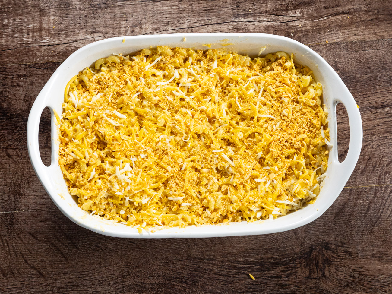 Pour macaroni into a deep 9x13 casserole dish or baking pan. Cover with sauce and stir to coat. Top with crushed crackers and the reserved cheeses.