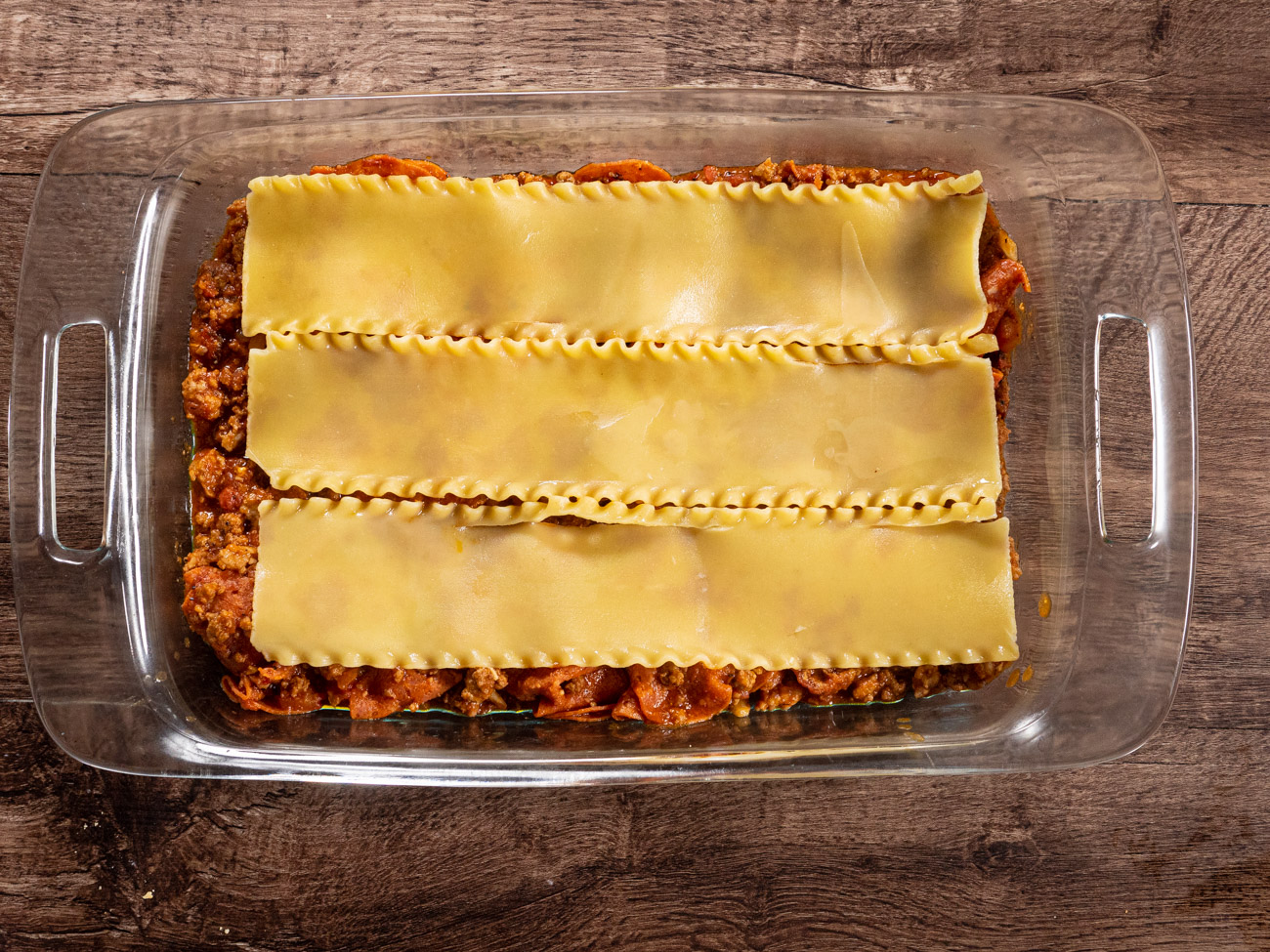 Spread sauce on bottom of a 9x13 baking pan or casserole dish. Layer noodles, ricotta, mozzarella, and parmesan. Repeat process starting with sauce, then noodles, and ending with cheeses.
