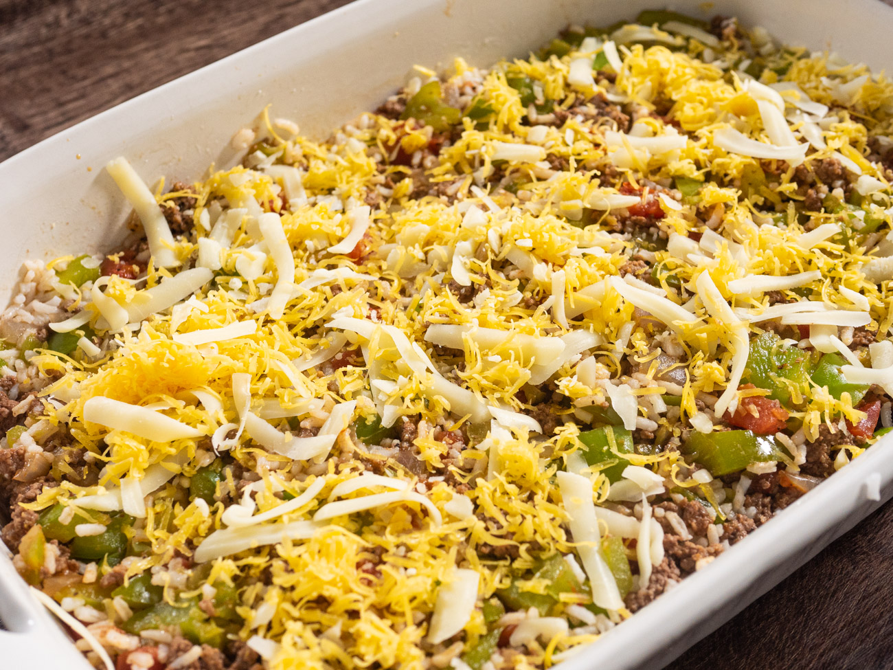 Remove skillet from heat. Stir in cooked rice, then immediately pour mixture into the prepared casserole dish and top with shredded cheese.
