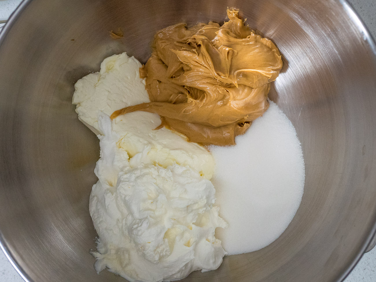 In a large bowl combine cream cheese, 1 cup peanut butter, and sugar and blend with an electric mixer. Fold in frozen whipped topping or whipped cream.