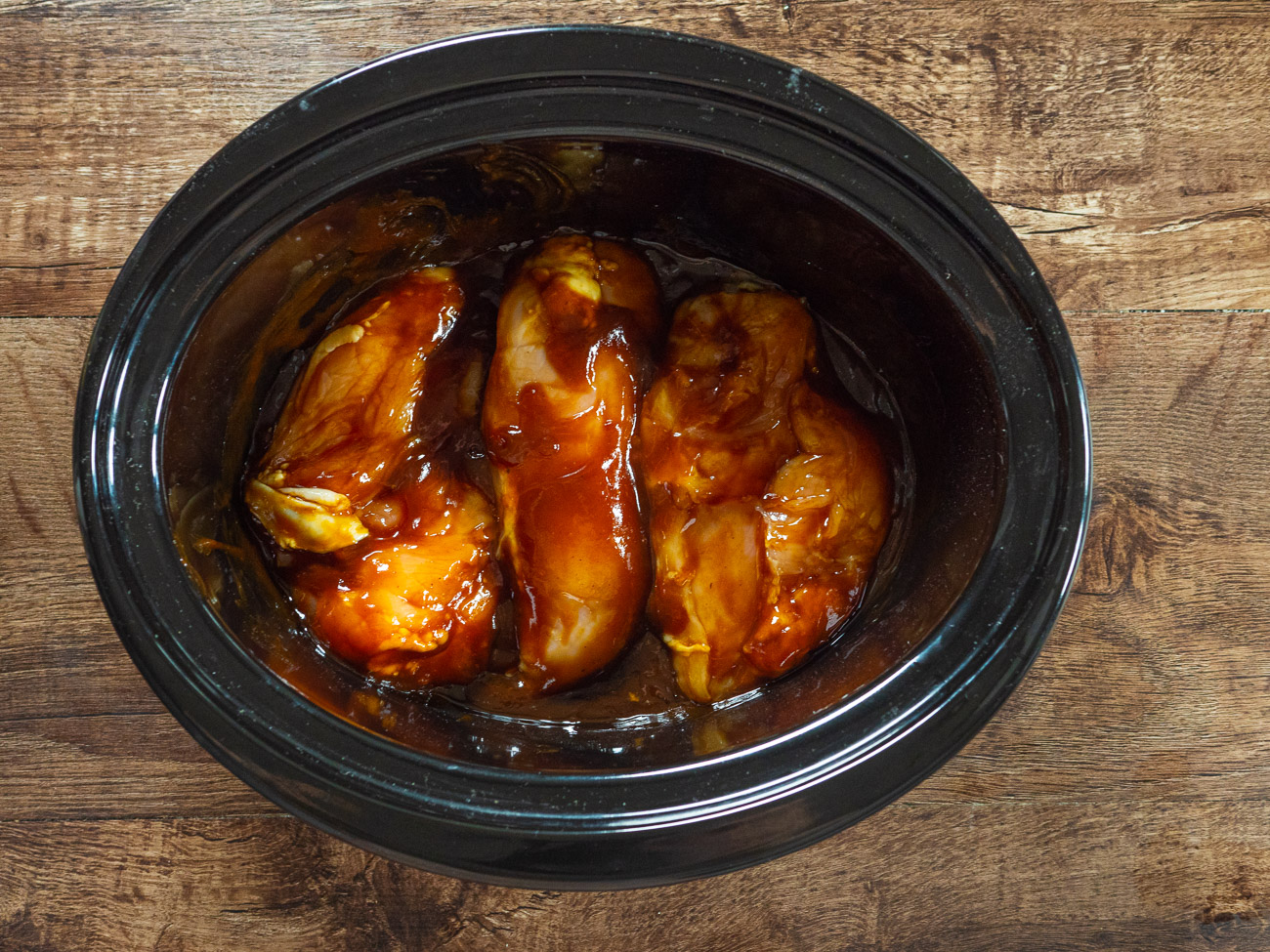 Place chicken in Crock Pot. Pour in oil and flip chicken to coat. Cover with barbecue sauce.
