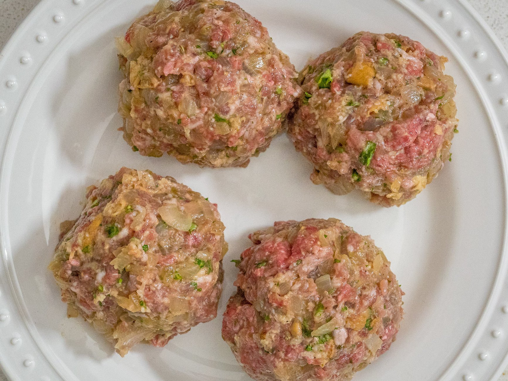 Knead mixture until completely blended. Divide into 4 equal parts and shape into balls. Then slightly flatten the frikadellen into patties. Chill patties for 30 minutes.