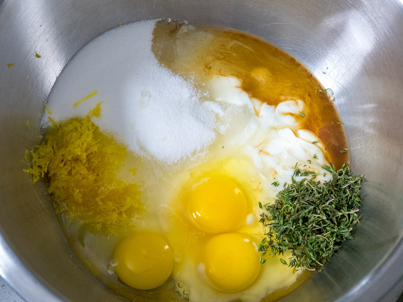 In a separate medium bowl combine yogurt, sugar, eggs, lemon zest, thyme, vanilla, and olive oil and stir. Gently fold in the flour mixture into the wet ingredients until just incorporated.