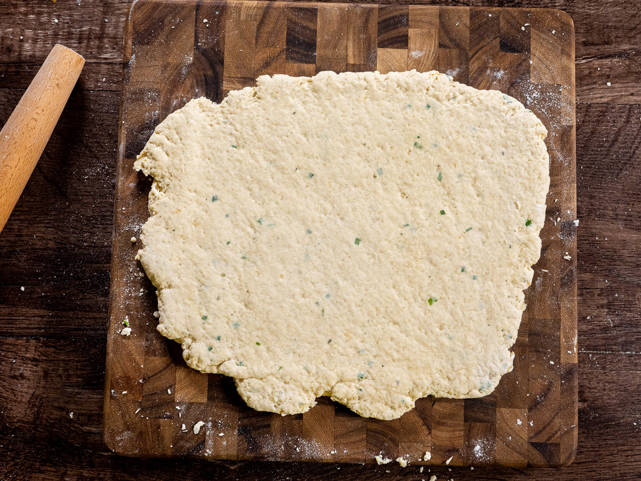 """Flour a work surface and pour dough out. Folded and knead 6 times, using more flour as needed. Roll out dough to 1/2"""" thickness and use a 2-inch round cookie cutter to cut out dough."""