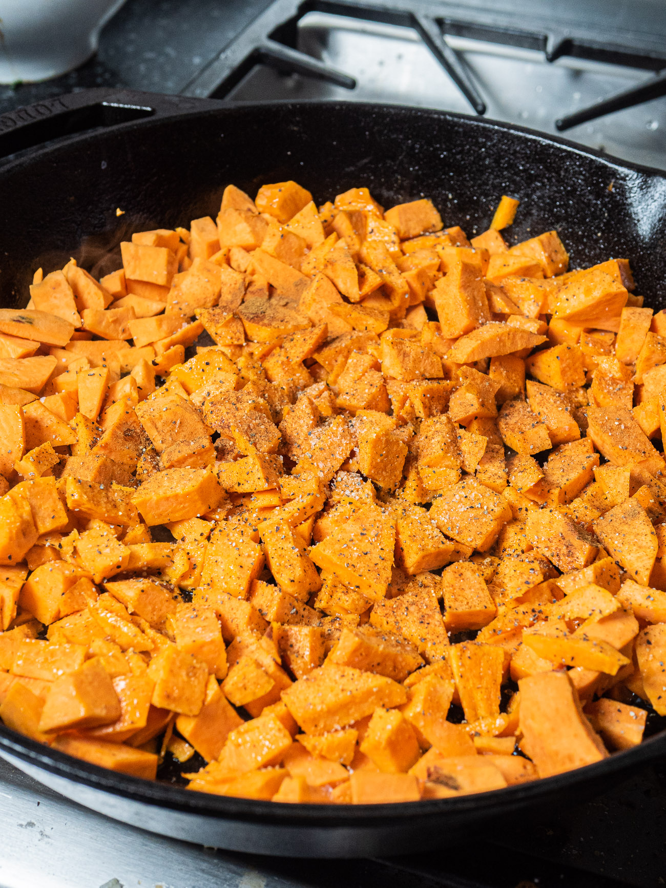 Add diced sweet potatoes to the skillet and sprinkle with cinnamon, salt, and pepper. Cook for 5 minutes before adding the diced green pepper and onion.