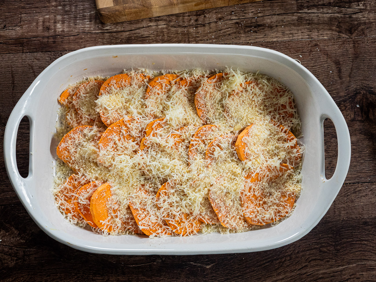 Arrange half of the potatoes in bottom of baking dish. Sprinkle with salt and pepper and half of the cheeses. Top with remaining potatoes and season again with salt and pepper.