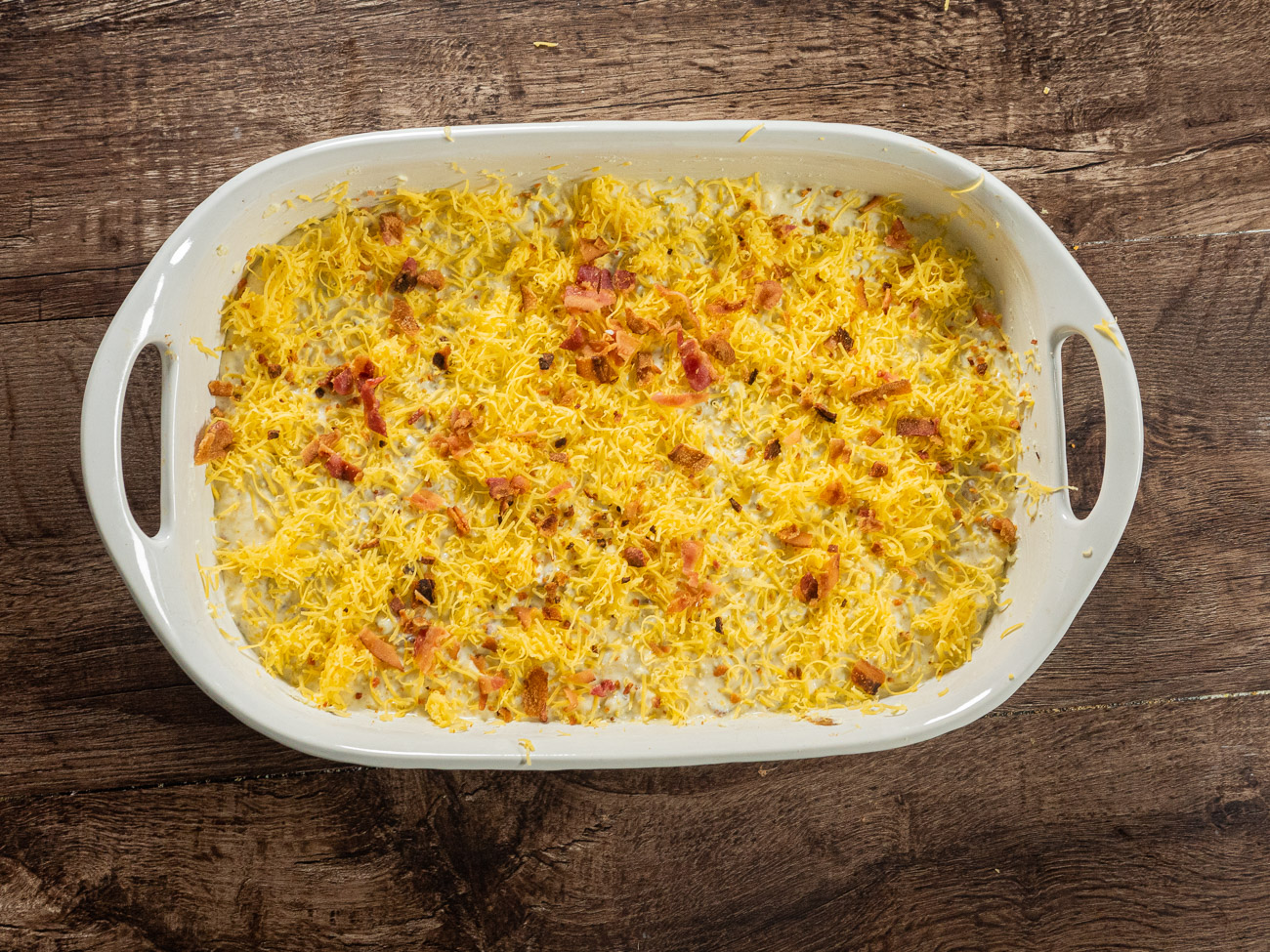 Pour mixture into prepared baking dish and top with remaining bacon and cheese. Bake until center is set and top is golden brown, 40-45 minutes. Enjoy!