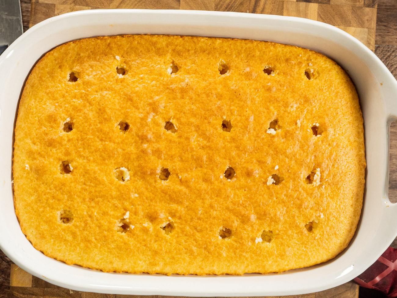 """Prepare cake to box instructions in a 9""""x13"""" cake pan. Poke regularly-spaced holes in the cake using chopstick or skewer. Allow to cool."""