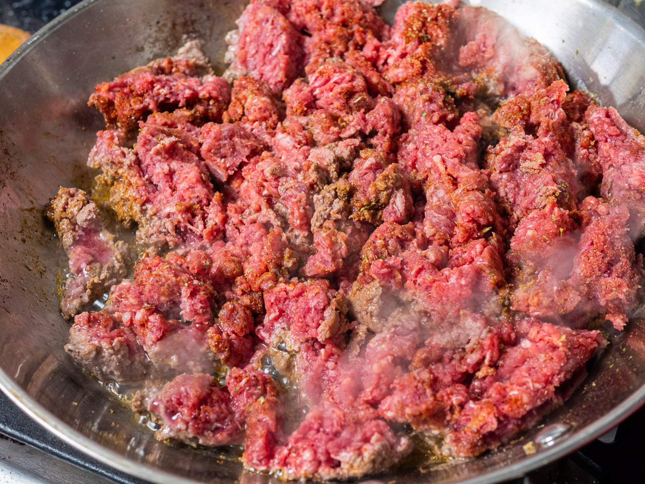 Brown ground beef in a skillet, seasoning it with garlic powder, Italian seasoning, paprika, and chili powder. Drain excess fat and set aside.