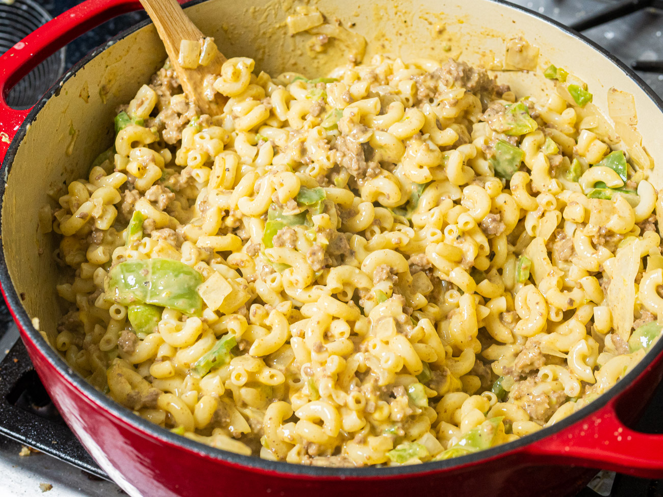 Once onions and peppers are done cooking, stir in ground beef mixture. Slice up Velveeta and add to the same skillet, stirring until melted and smooth.