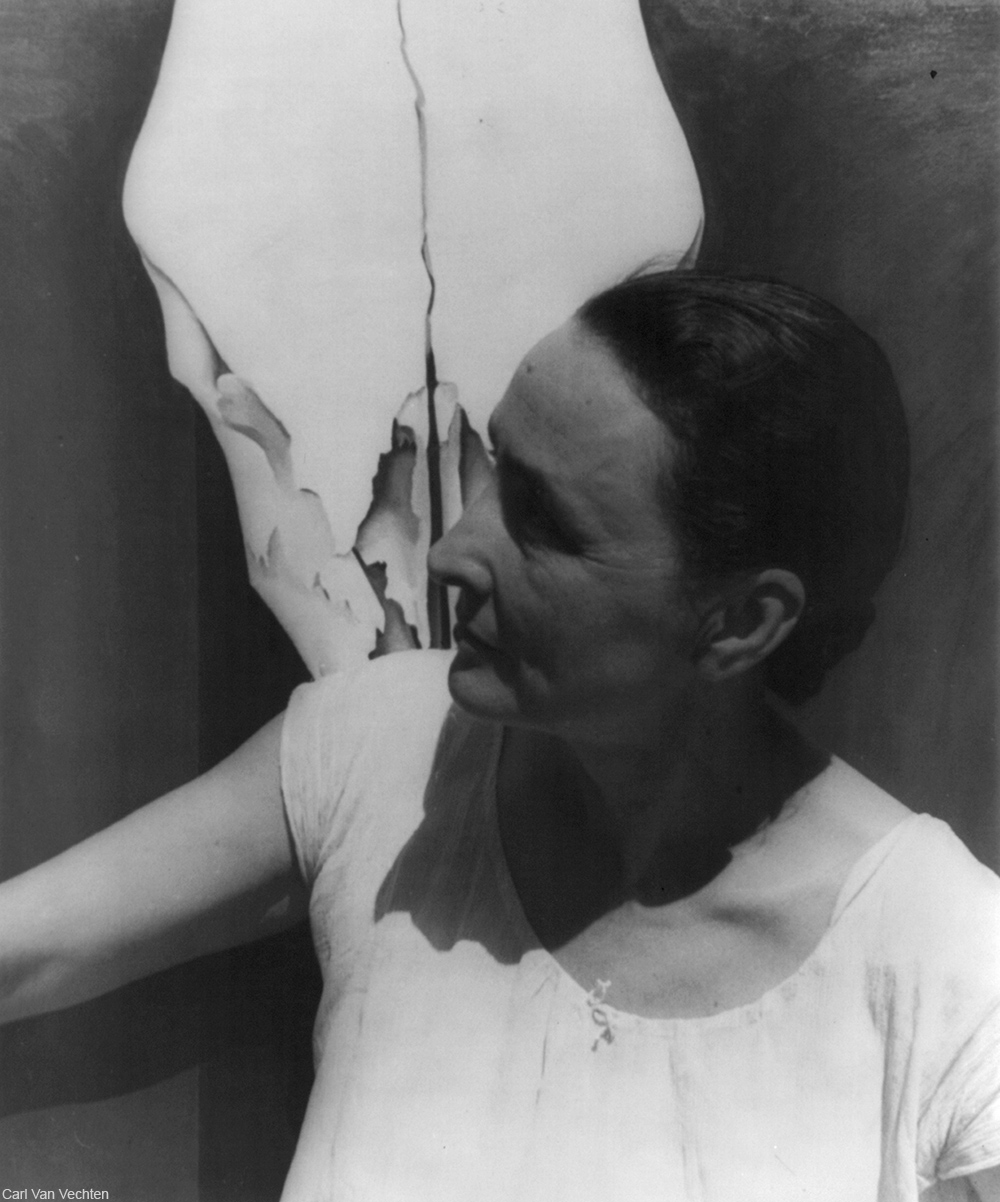 Georgia O'Keeffe photographed in front of one of her paintings
