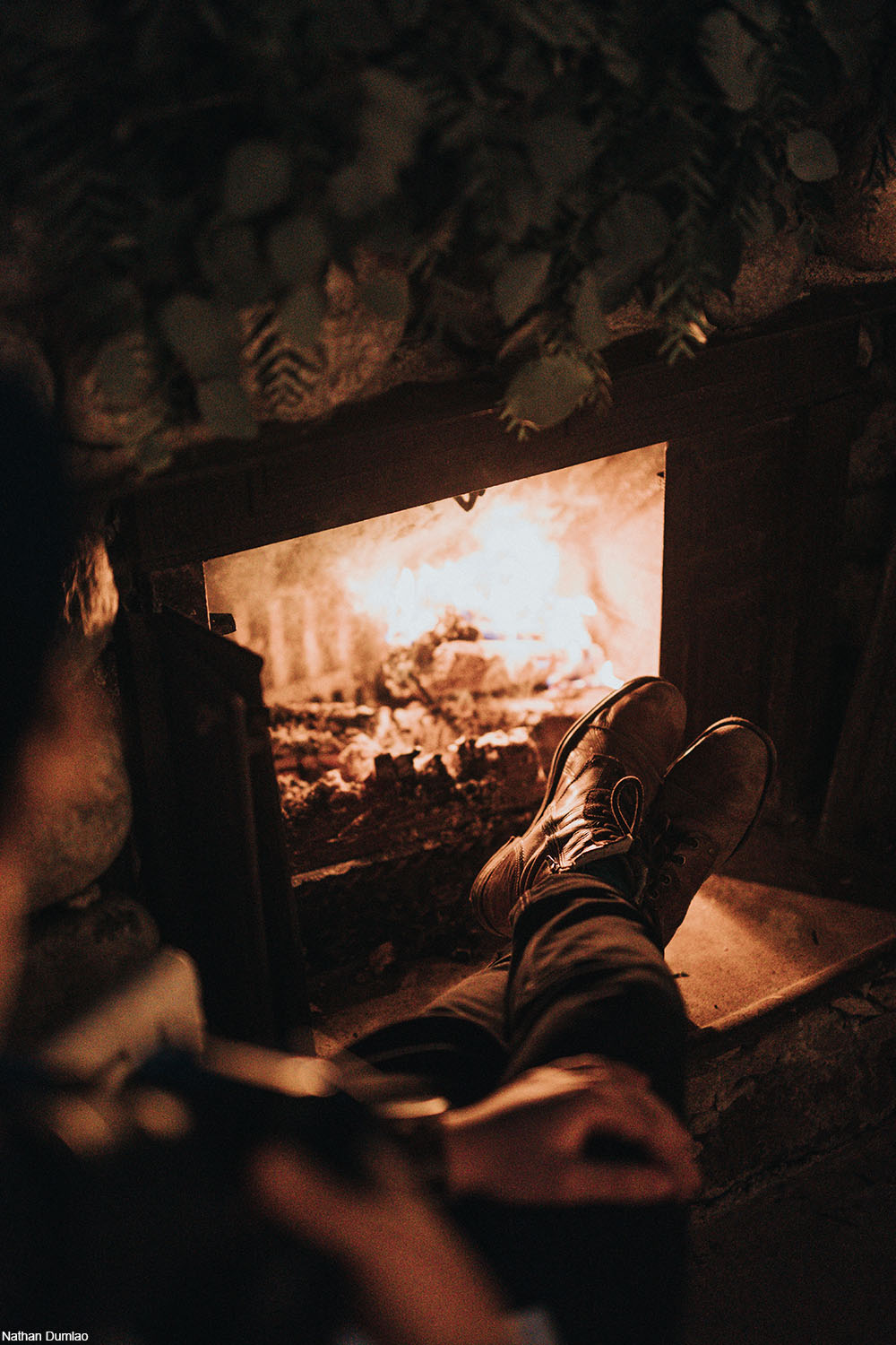 person relaxing in front of a fire