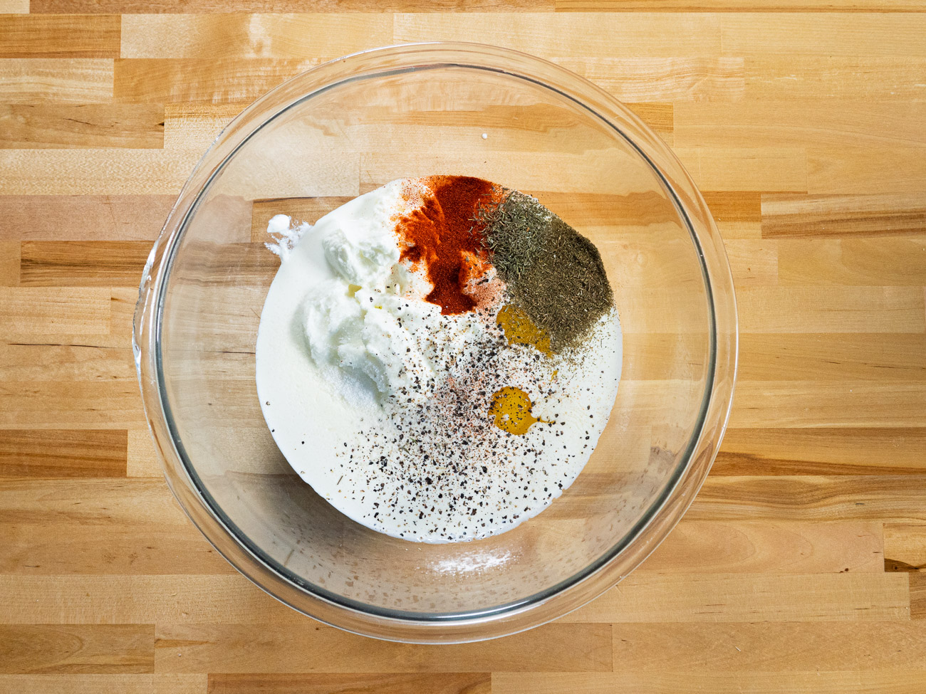 In a very large bowl whisk together cream, yogurt, eggs, melted butter, and spices.