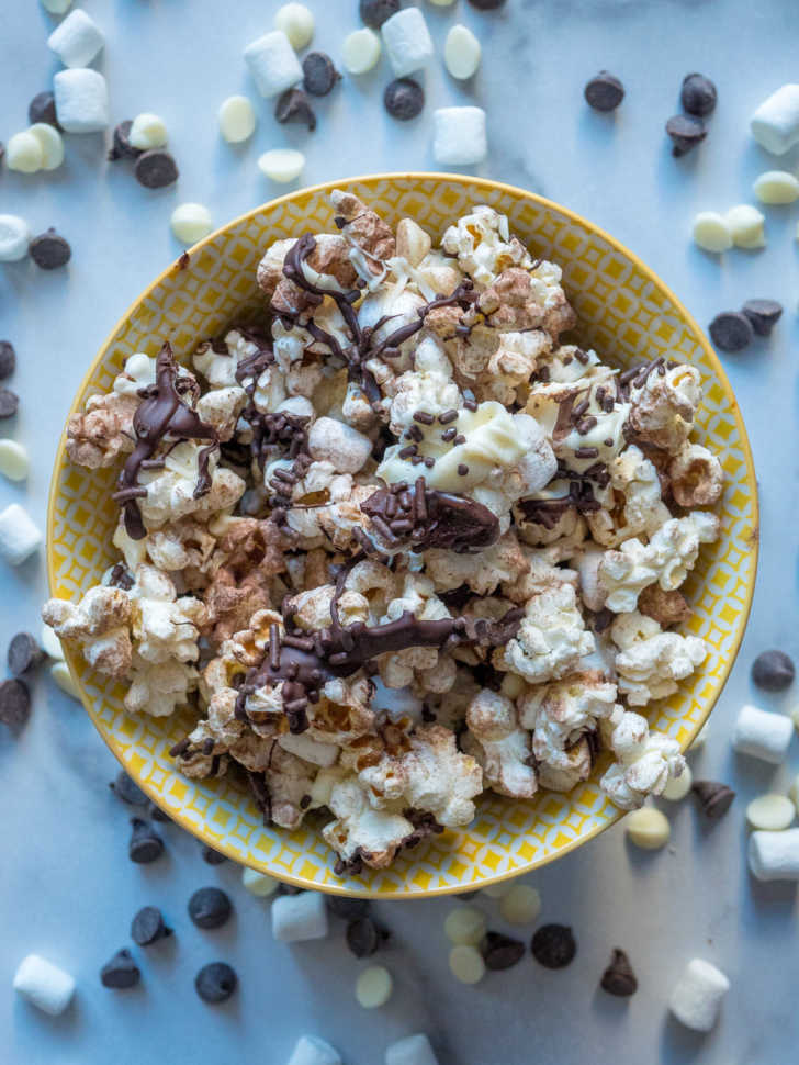 Bowl of popcorn with chocolate drizzled and cocoa powder sprinkled on top