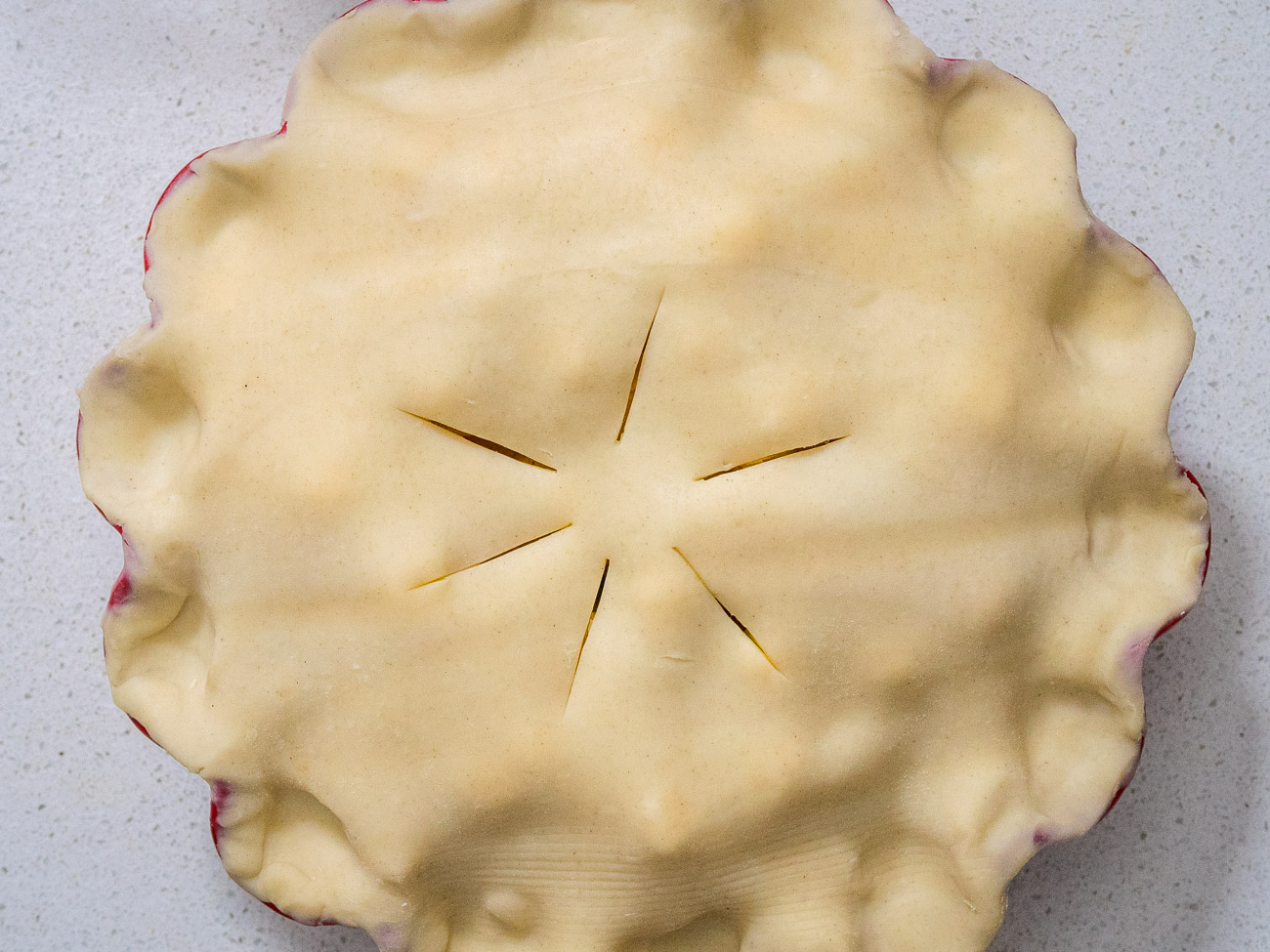 Carefully lay the other crust over the filling. Trim the excess crust from around the edges. Cut slits in the top to form steam vents. Crimp the edges to seal.