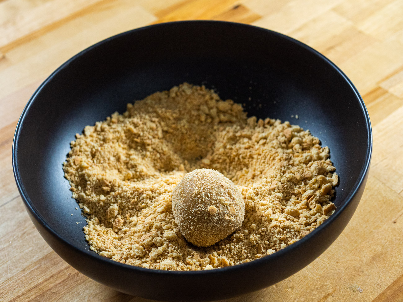 Place 1/2 cup graham cracker crumbs in a shallow bowl. Then, using a small spoon or cookie scoop, scoop the cookie dough and roll in graham cracker crumbs.