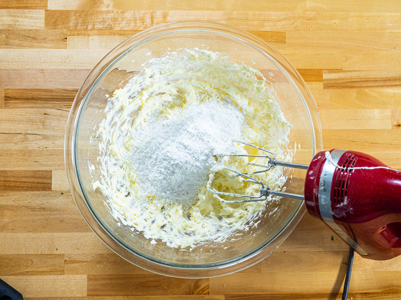 Using a hand mixer, beat butter and cream cheese until smooth and combined. Then, beat in powdered sugar, one cup at a time, then add vanilla and lemon zest.