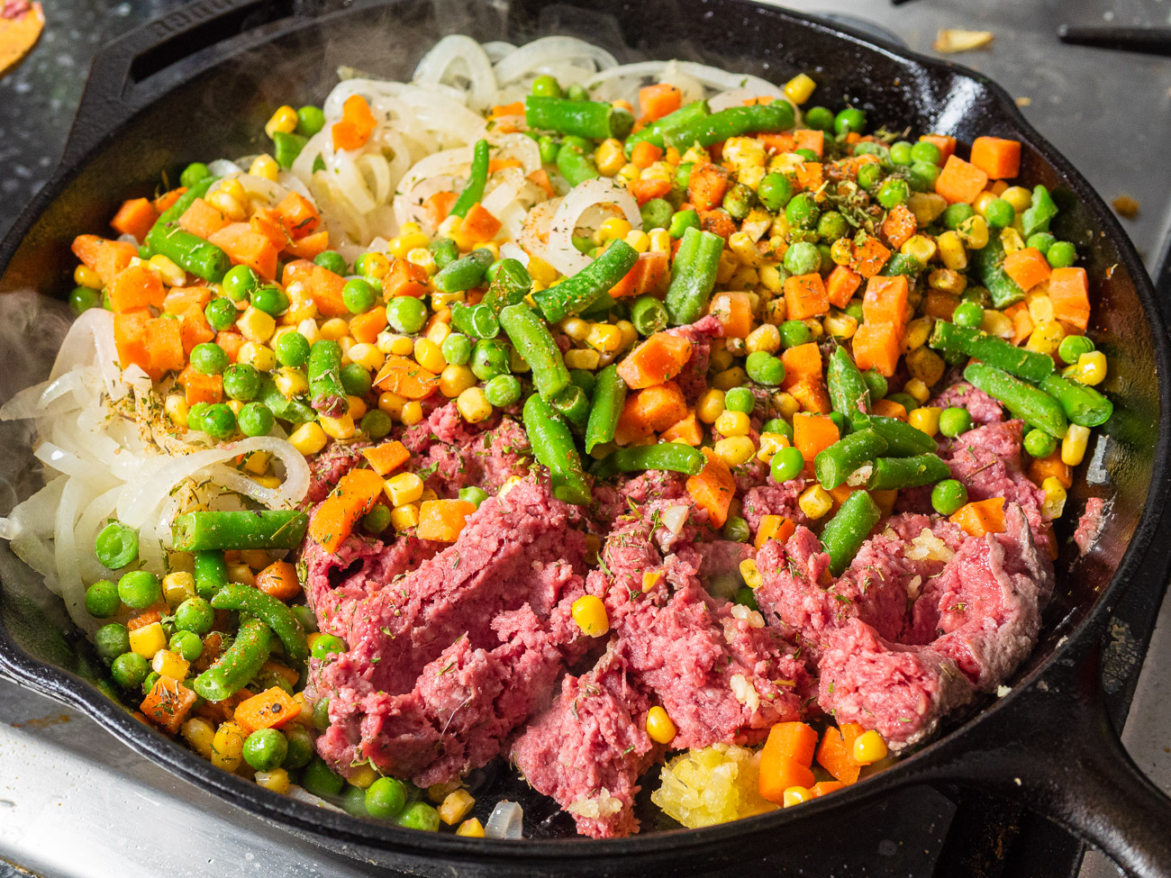 Push the onions to the side of the pan and stir in ground beef, thawed veggies, garlic, thyme, parsley, cayenne, and season with salt and pepper. Cook, breaking up the meat as it cooks, another 5 minutes until the meat is browned.