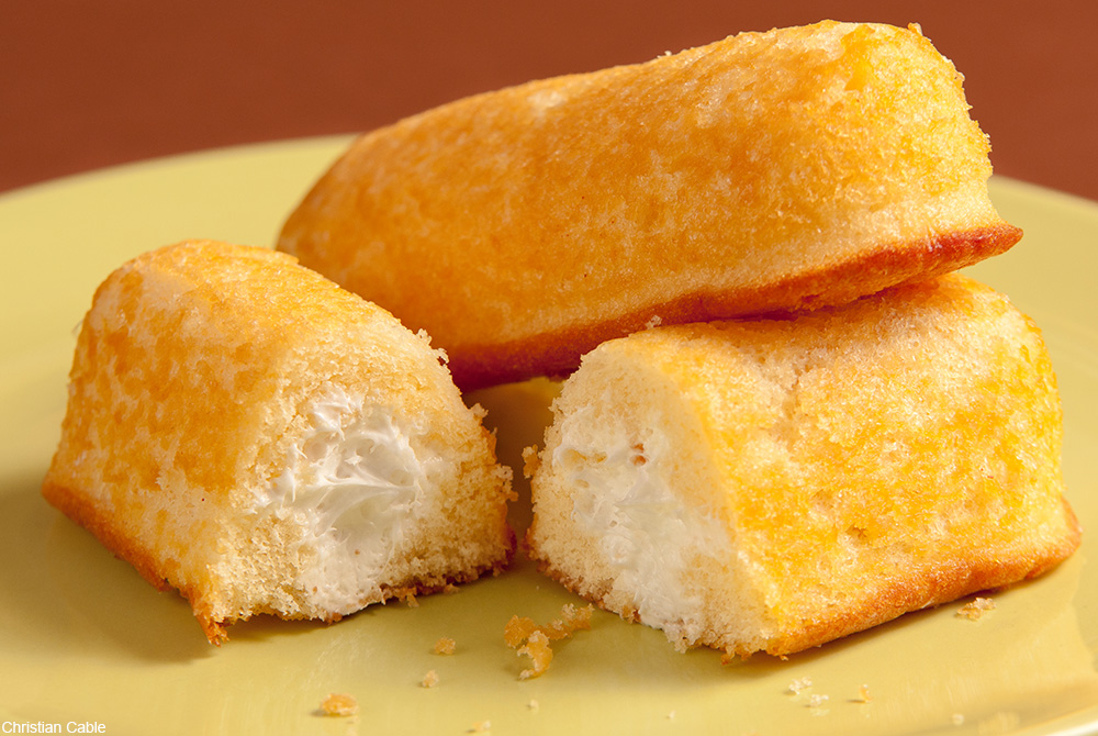 Twinkies stacked on a yellow plate
