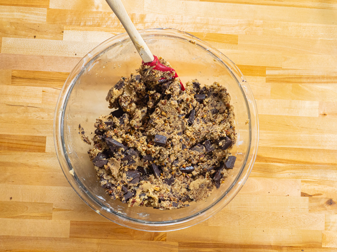 With a spatula or wooden spoon, gently fold in the flour mixture until just combined. Fold in the chocolate chunks and buttered pecans.