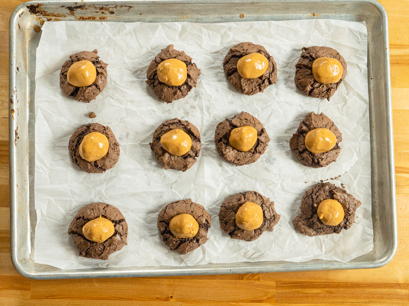 As soon as the cookies come out of the oven, press a peanut butter ball lightly into the center of each cookie. The peanut butter mixture will soften slightly. Cool for about 5 minutes, then transfer to a wire rack.