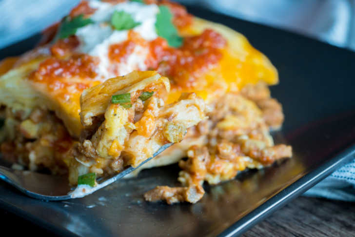 Serving of burrito casserole on a plate with sour cream on top