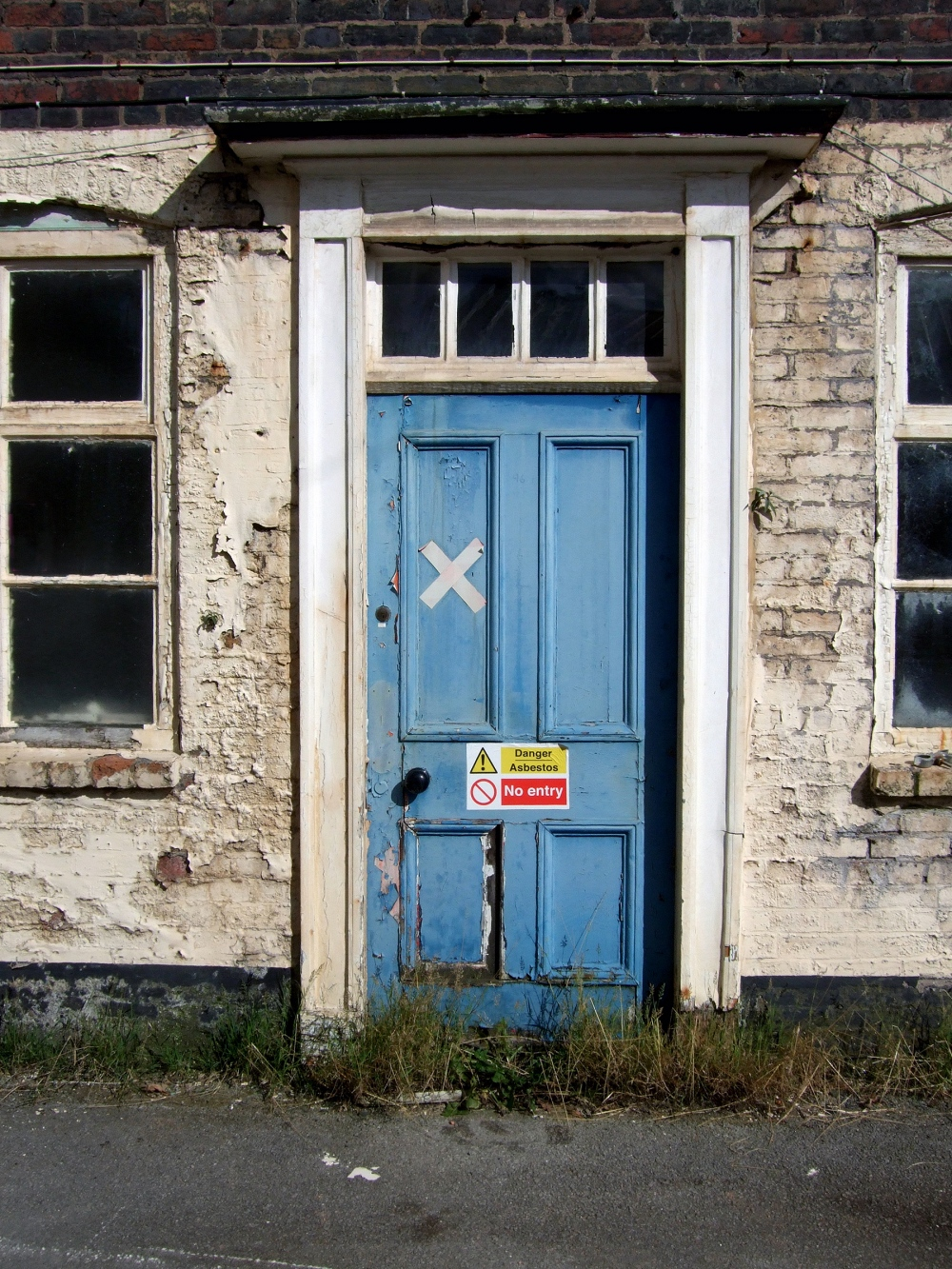 old house with asbestos warning on front door