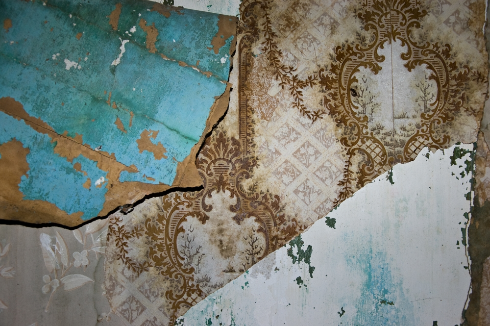 layers of peeling wallpaper in an abandoned house