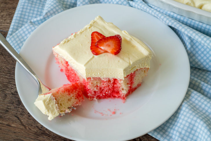 Top down view of strawberry cake on a plate with thick frosting