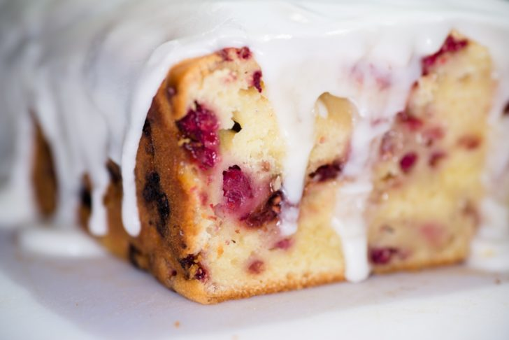 Close up of raspberry bread loaf with lemon icing drizzling down
