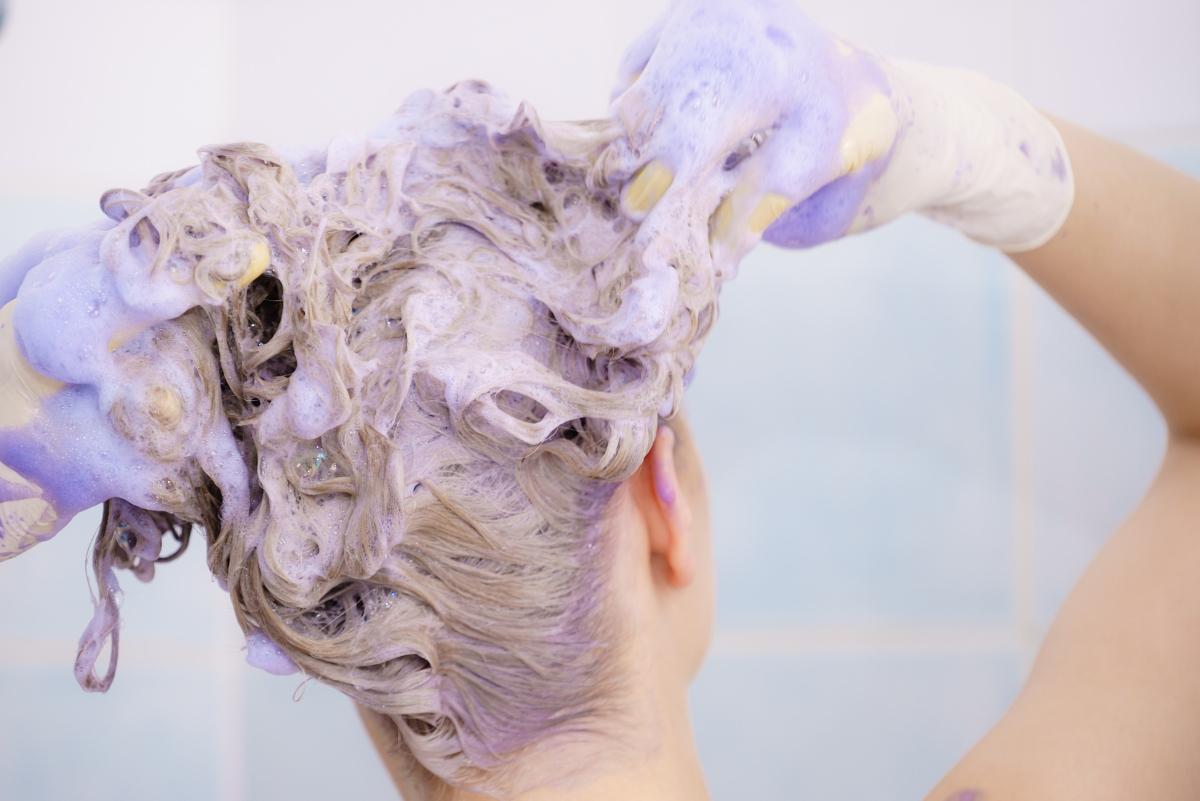 woman using purple shampoo in the shower