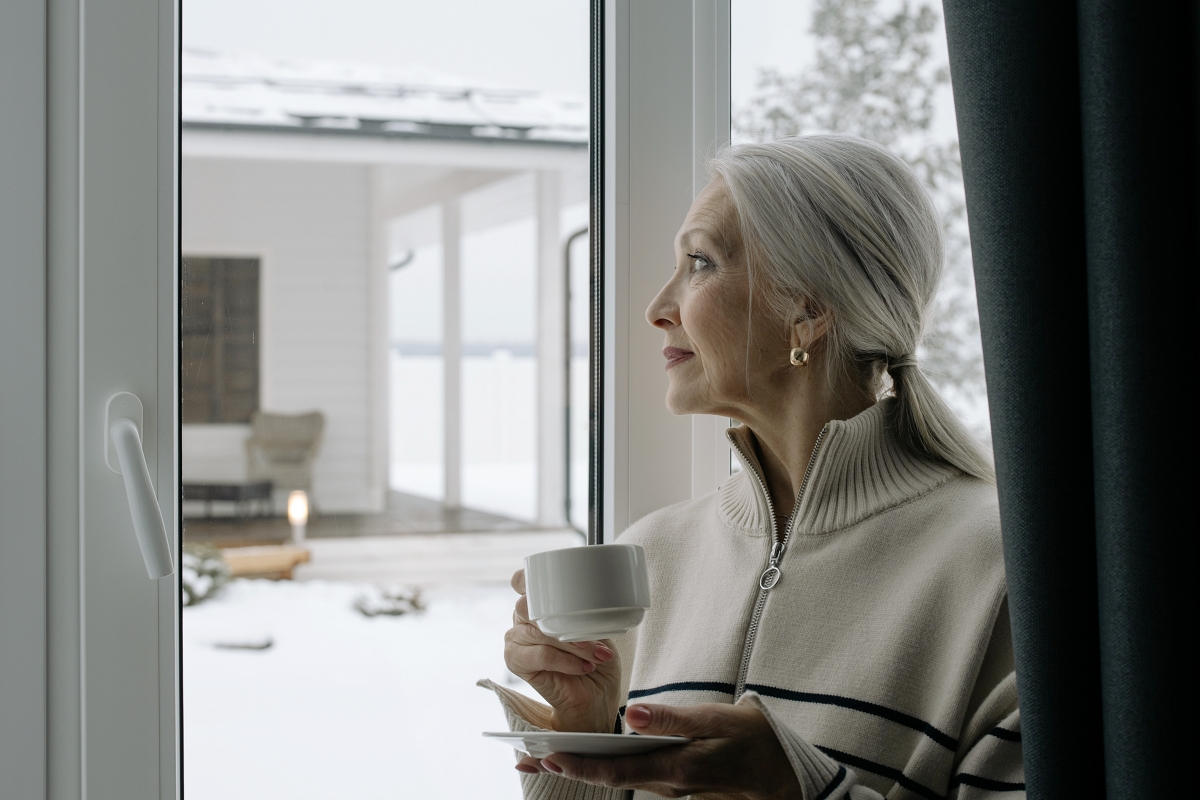 woman with silver hair sitting at a window