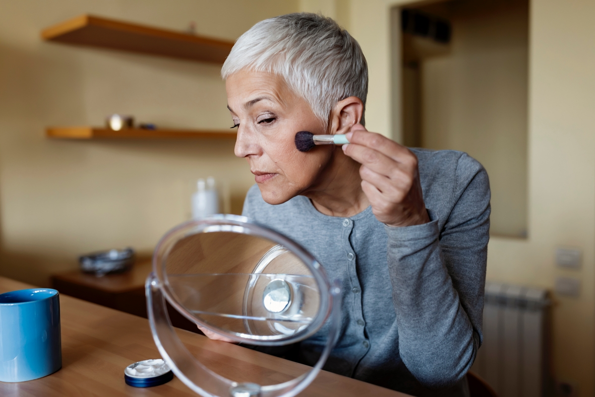 woman with grey hair applying blush to her cheeks