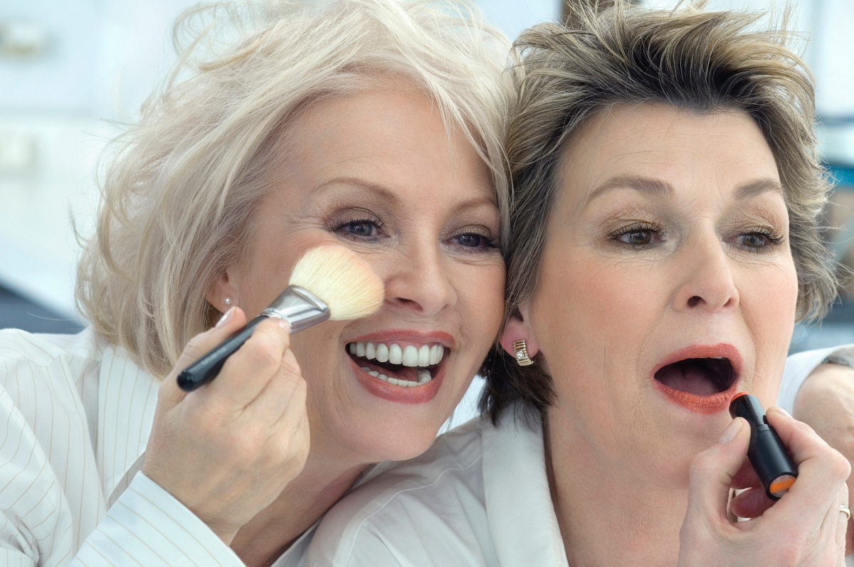 2 mature women applying makeup