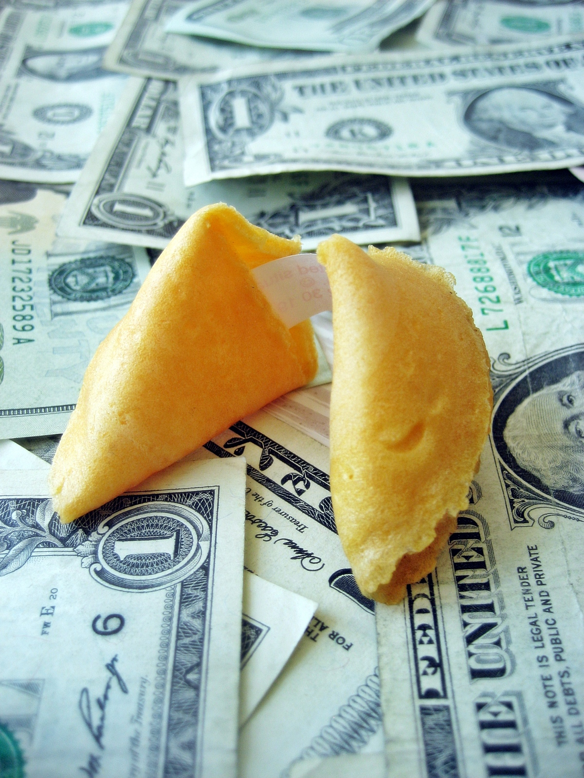 fortune cookie sitting on a pile of money